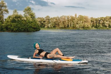 attractive tattooed girl with blue hair relaxing on paddle board on river