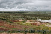 Fotografie scenic view of landscape with volcanic vents under cloudy sky in Haukadalur valley in Iceland