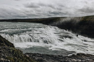 aerial view of beautiful Gullfoss waterfall under cloudy sky in Iceland