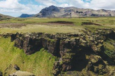 İzlanda'daki mavi bulutlu gökyüzü altında dağlar aralığıyla manzara