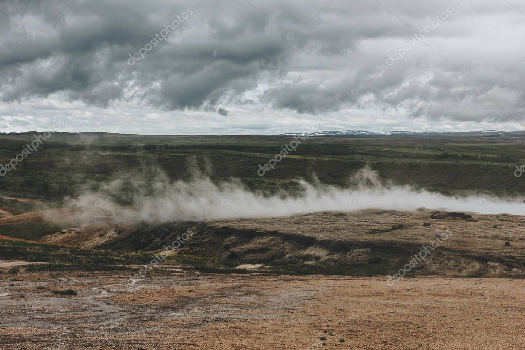 scenic view of landscape with volcanic vents under cloudy sky in Haukadalur valley in Iceland