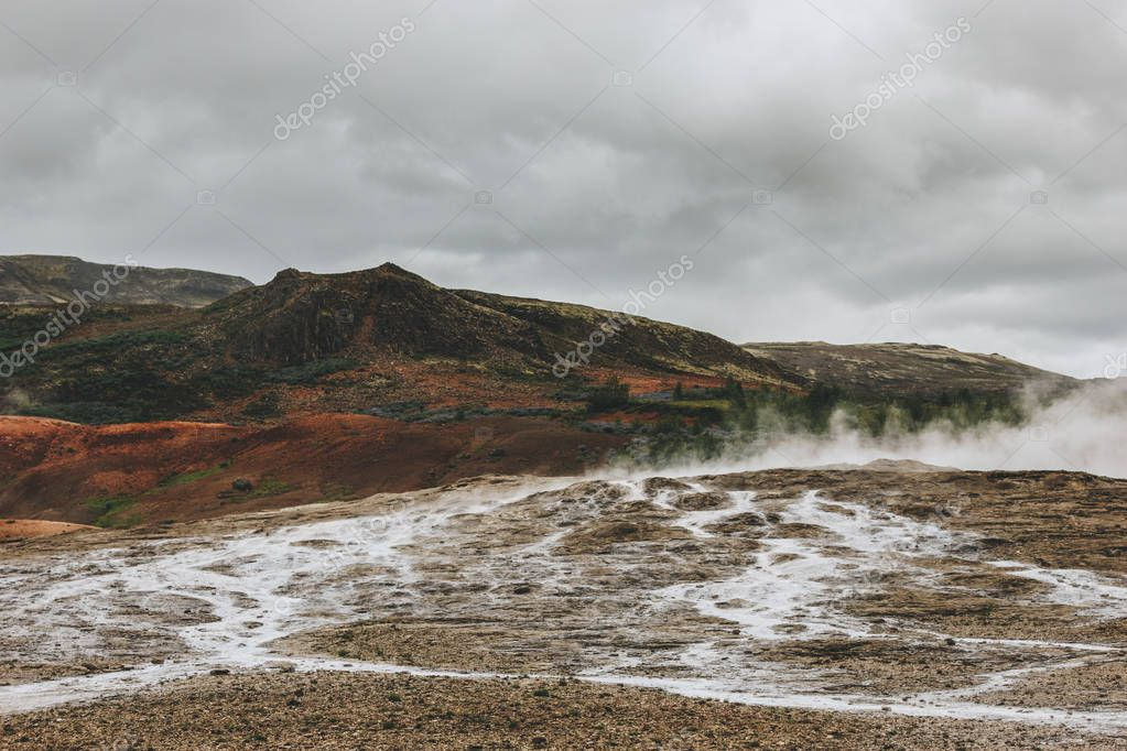 beautiful landscape with volcanic vents under cloudy sky in Haukadalur valley in Iceland