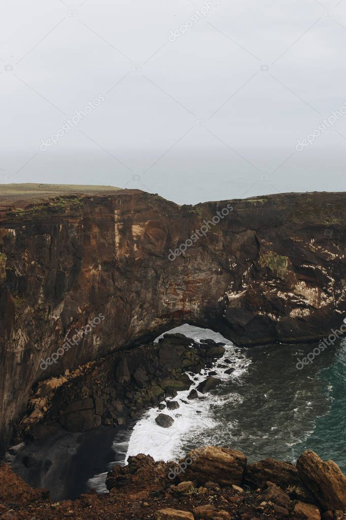 Фотообои aerial view of rocky cliff and ocean under cloudy sky at Dyrholaey promontory in Vik, Iceland