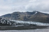 Fotografie glacier Skaftafellsjkull and snowy mountains against cloudy sky in Skaftafell National Park in Iceland