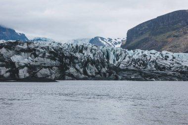 Glacier Skaftafellsjkull and snowy mountains against cloudy sky in Skaftafell National Park in Iceland stock vector
