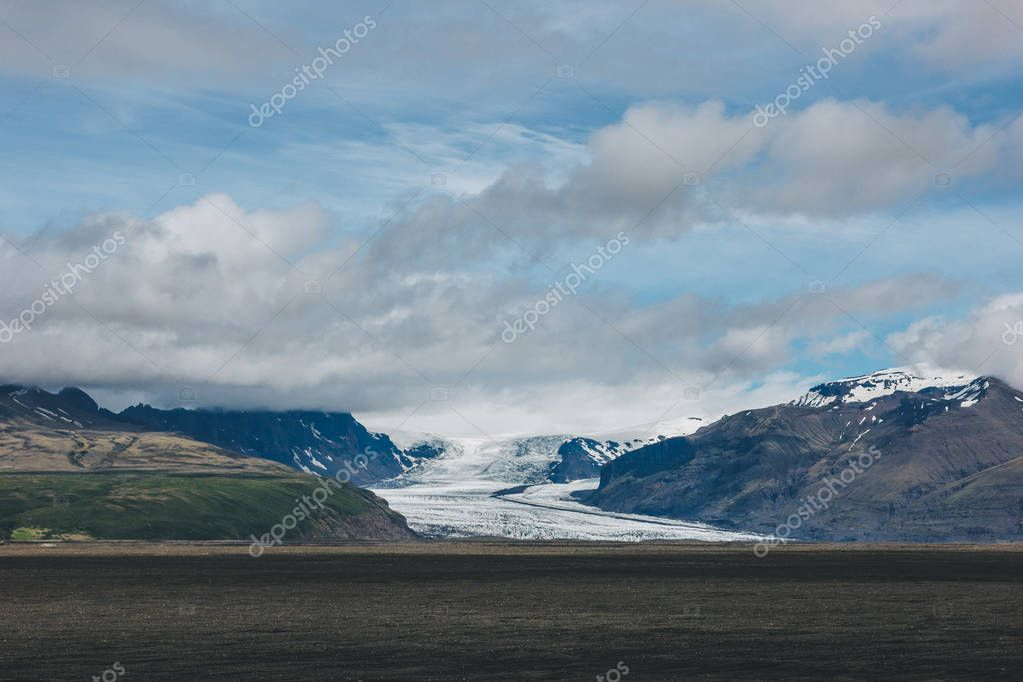Фотообои scenic view of landscape with mountains covered by snow under cloudy sky in Iceland