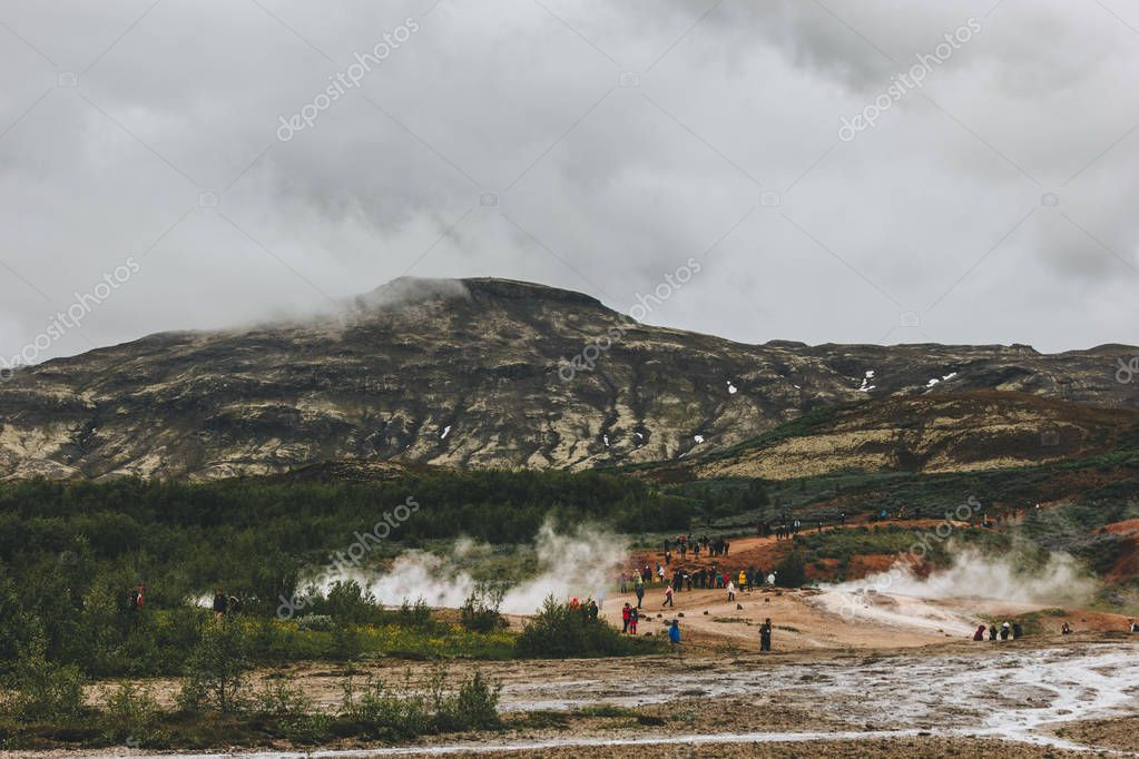 ICELAND - 20 JUNE 2018: distant view of tourists near volcanic vents in Haukadalur valley