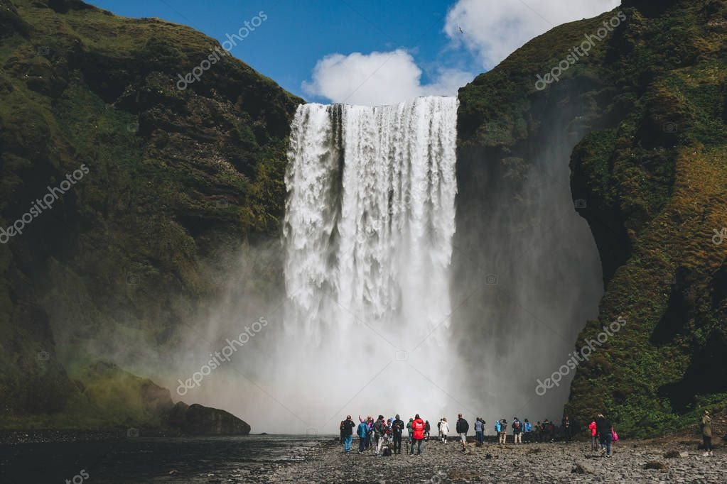 ICELAND - 20 JUNE 2018: tourists walking near waterfall Skogafoss under bright blue sky