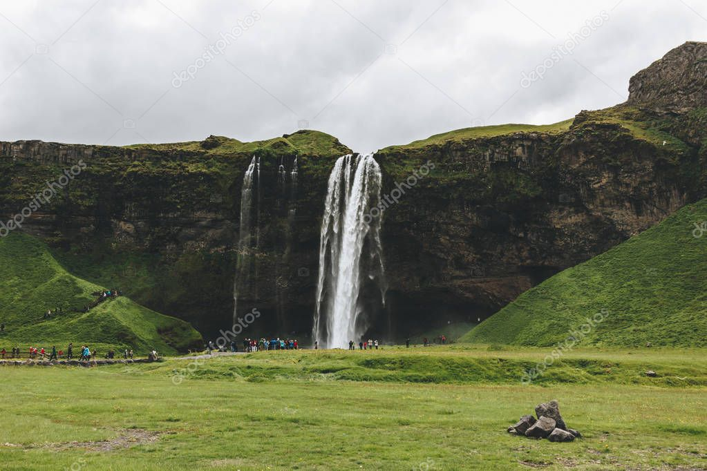 ICELAND - 20 JUNE 2018: beautiful waterfall Seljalandsfoss and tourists under cloudy sky