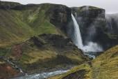 islandský krajina s Haifoss vodopádu a zelené kopce na mlhavý den