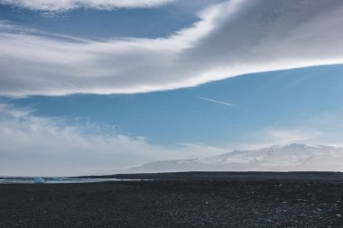 Black volcanic sand on ocean coast of Jokulsarlon, Iceland under blue sky with clouds stock vector