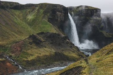 icelandic landscape with Haifoss waterfall and green hills on misty day
