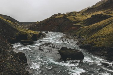 river streaming in green mountains in Iceland on misty day