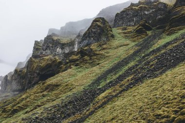 dramatic shot of mountain with green grass and rocks in Iceland on misty day