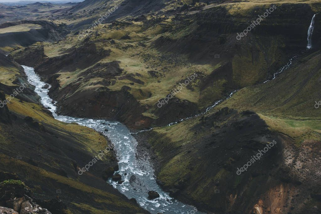 aerial view of curvy river streaming in green hills in Iceland
