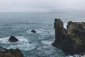 skalnaté útesy před modrý oceán v Arnarstapi, Island na zamračený den
