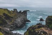 malebný pohled krásných útesů před modrý oceán v Arnarstapi, Island na zamračený den