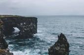 dramatický snímek skalnaté útesy a bouřlivém oceánu v Arnarstapi, Island na zamračený den