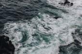 dramatický snímek z pěnivých mořských vln, shazovat na skalách pro pozadí