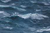 Photo dramatic shot of bird flying over wavy blue ocean