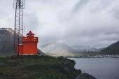 maják na útesu s rainbow na pozadí na Islandu