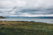 Fotografie scenic with of green meadow over large lake in Iceland