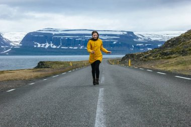 Young woman running by empty road in iceland with beautiful mountains and lake on background stock vector