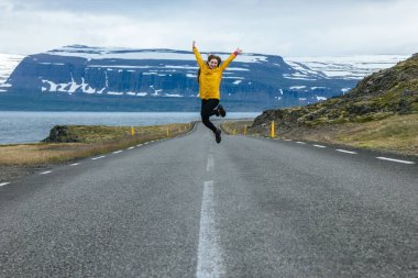 Young woman jumping on empty road in iceland with beautiful mountains and lake on background stock vector