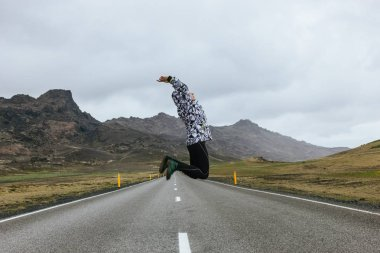 Young woman jumping on empty road in iceland with beautiful mountains on background stock vector