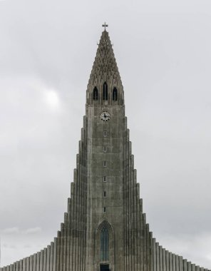 REYKJAVIK, ICELAND - 22 JUNE 2018: spire of beautiful Hallgrimskirkja church in Reykjavik on cloudy day stock vector