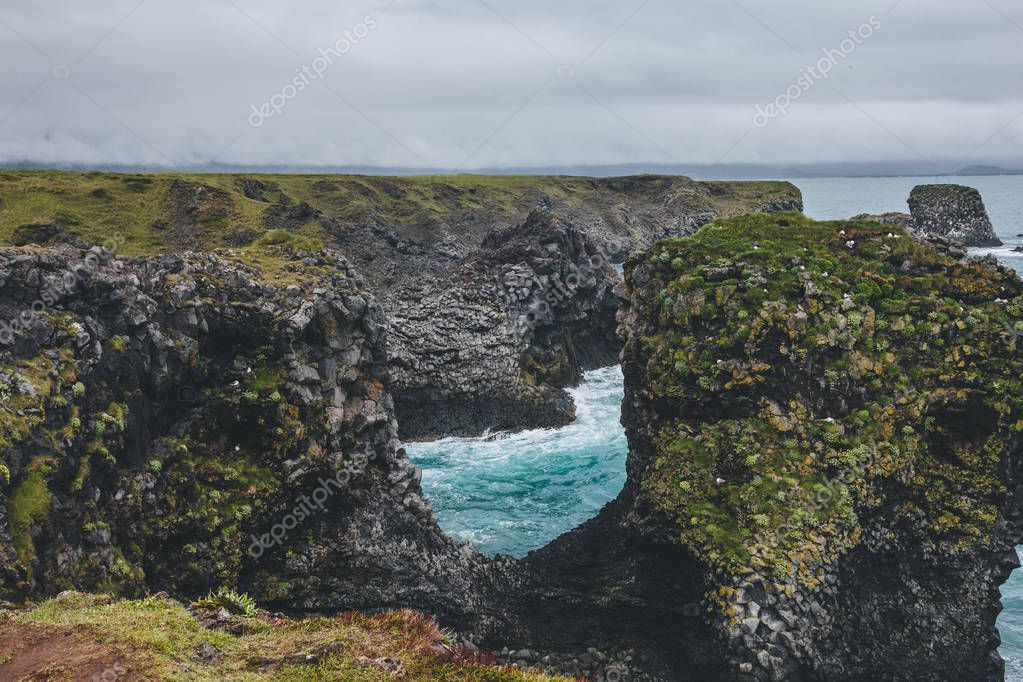 beautiful mossy cliffs in front of blue ocean in Arnarstapi, Iceland on cloudy day