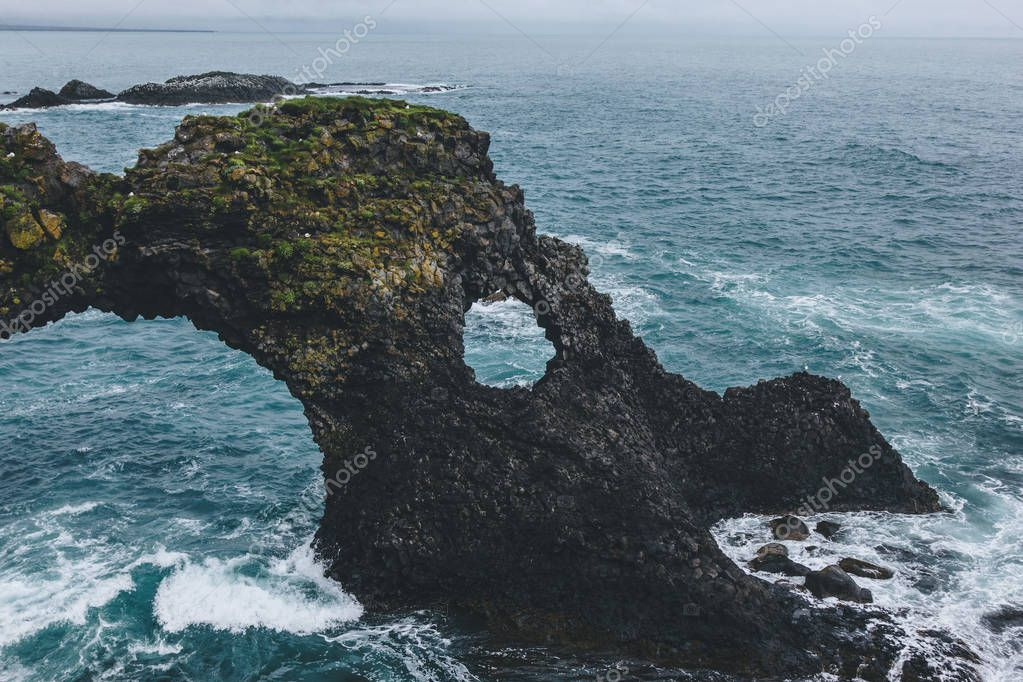 beautiful mossy cliff in front of blue ocean in Arnarstapi, Iceland