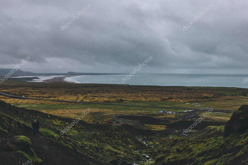 ICELAND - 22 JUNE 2018: scenic with of icelandic coast and green valley with crowd of tourists