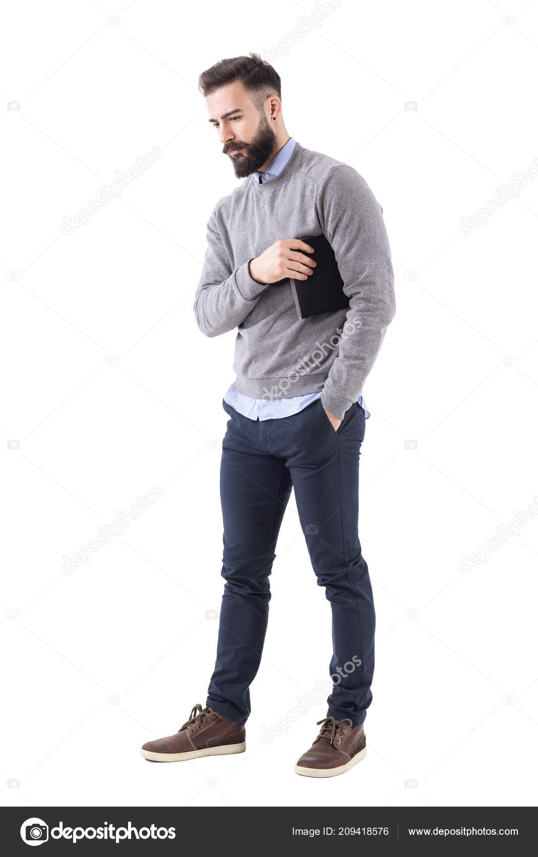 7c6666e25e Serious thoughtful business man carry notebook under the arm and looking  down. Full body length portrait isolated on white studio background.