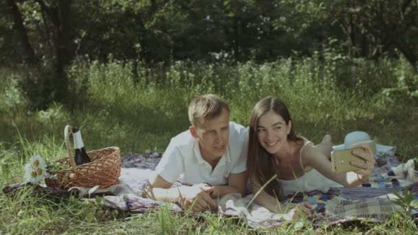 Smiling couple taking selfie on smart phone on picnic