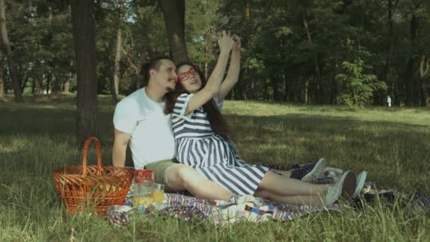 Carefree pregnant couple taking selfie in nature