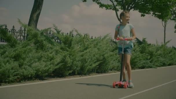 Šťastná holčička jezdecké koloběžka v parku