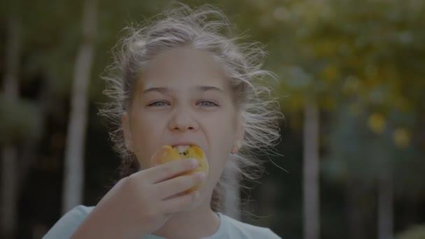 S úsměvem roztomilý nedospělý dívka venku jíst broskev