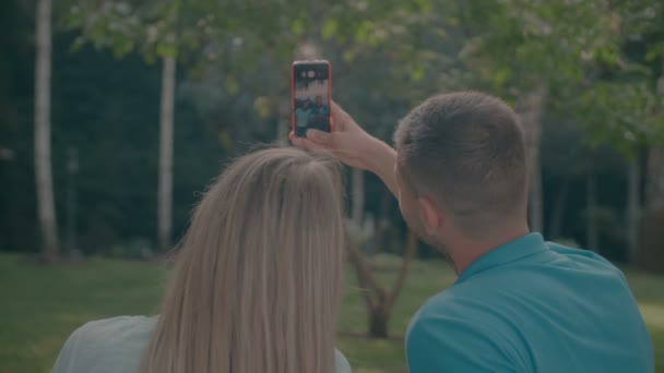 Smiling couple with cellphone taking selfie in park