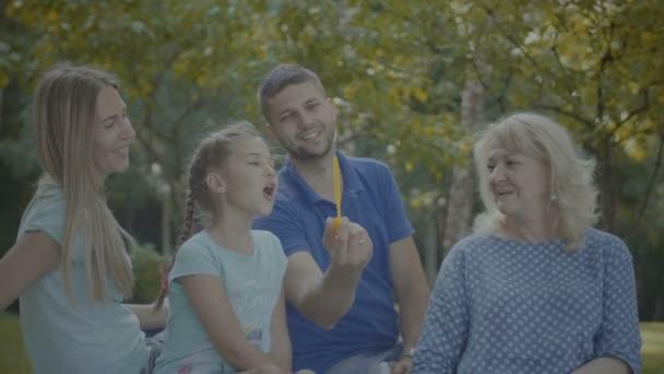 Tři generace rodiny hrát s mýdlové bubliny