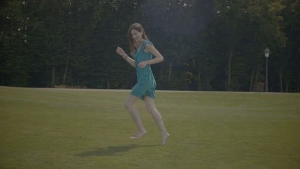 Excited barefoot girl running along green field