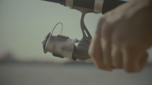 Horgász kezében csavaró orsóhoz