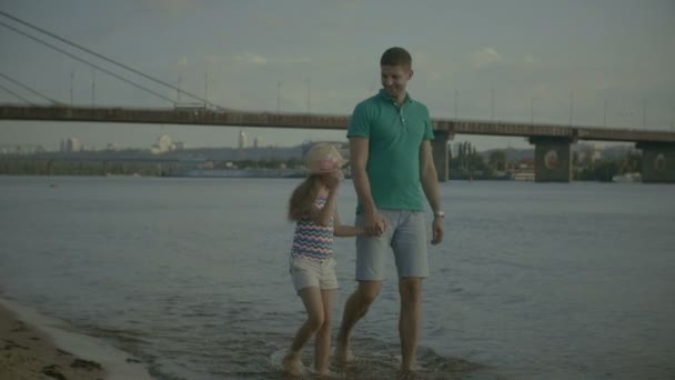 Carefree father and daughter walking on beach