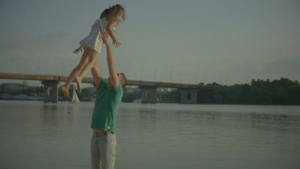 Joyful father throwing up in the air his daughter