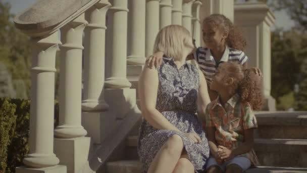 Joyful multi ethnic family resting on stairs