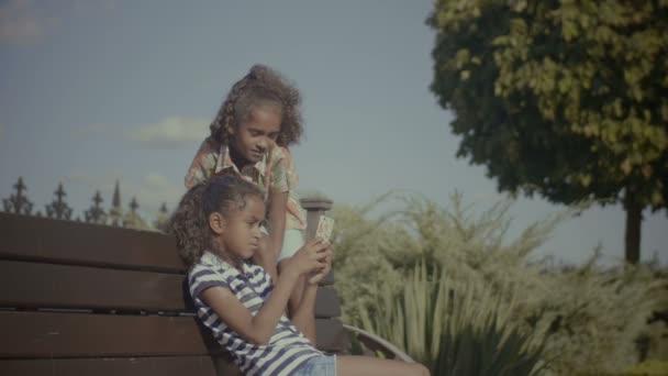 Veselé děti s chytrý telefon, sedí na lavičce