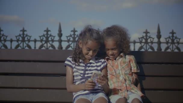 Děti chatovat online pomocí chytrý telefon na lavičce