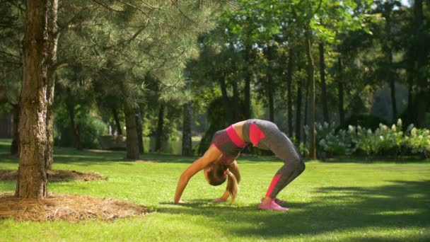 Fit sporty woman doing backbend exercise outdoors