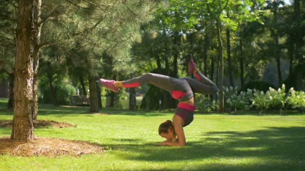 Sporty slim woman doing handstand exercise on grass