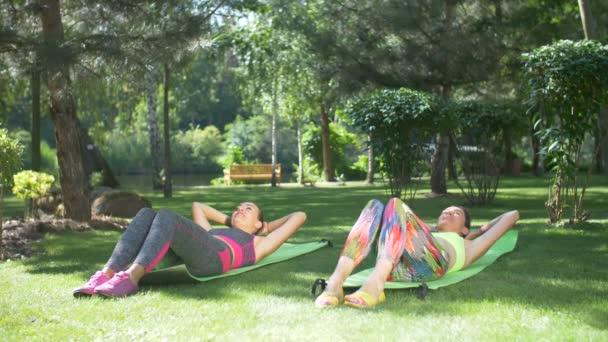 Aktivní ženy provádějící sit-up cvičení venku